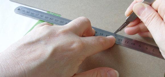 Skär ut kartongen du tänker använda som botten i asken. Använd en stållinjal och skalpell för att få raka kanter.