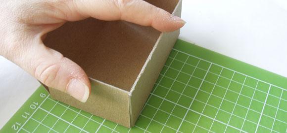 Vik upp sidorna på kartongen så att det formar en ask. Kolla så att sidorna är lika höga och testa så att kortleken får plats.