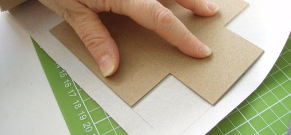 Använd kartongen för att mäta upp omslagspappret. Du kan använda en linjal som mått.