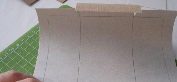 Omslagspappret skall vara större än kartongbiten till asken när du är färdig med att skära ut det.