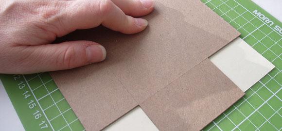 Använd kartongbiten som mall för att skära upp pappret till insidan.