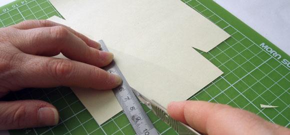 Använd en linjal för att göra små vinkar på flikarna som skall vikas runt hörnen.