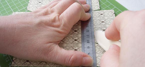 Använd falsbenet för att göra viklinjer längs med kanterna på pappret till insidan.