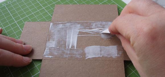 Stryk på lim på kartongbitens baksida, alltså det som blir undersidan av kartongen.
