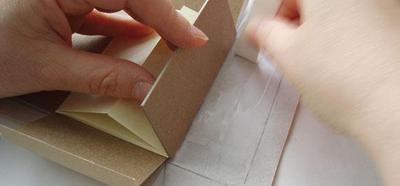 Börja limma fast omslagspappret på asken. Se till att limma det med sidorna i 90 graders vinkel.