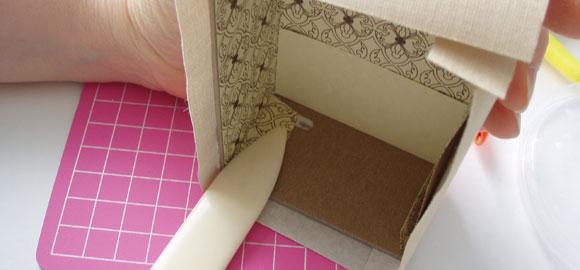 Använd falsbenet för att släta ut det limmade pappret.