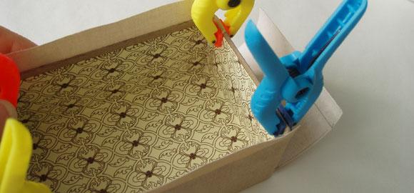 Börja limma ner omslagspappret över kanten på asken. Börja med bredsidorna igen.