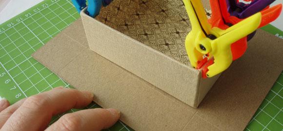 Använd asken som mall för att mäta ut pappen till locket. Locket behöver inte vara lika djupt som höjden på asken. Det räcker med en till två centimeter.